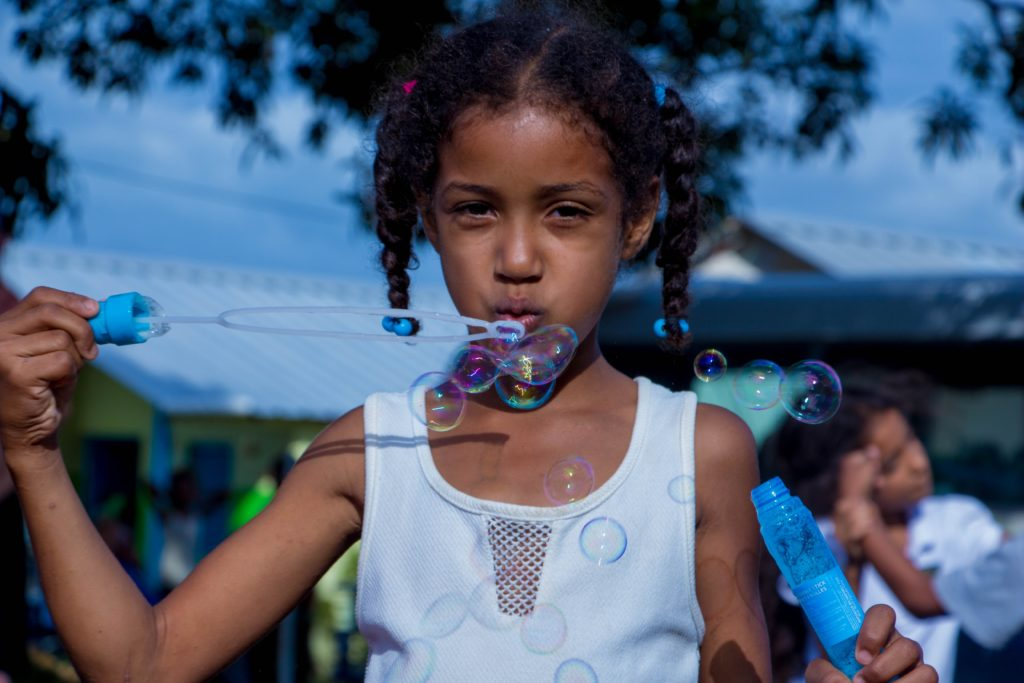 young girl outside blowing bubbles
