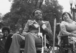 black and white image of black man wearing a suit in wheelchair speaking in microphone, sitting next to white woman in glasses in a wheelchair