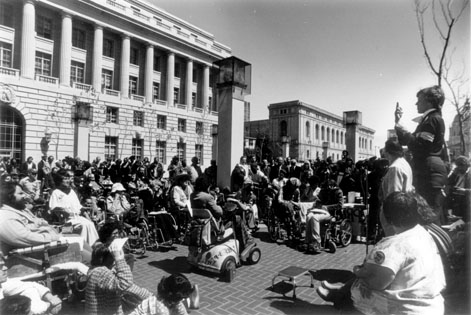 black and white photgraoh of people in wheelchairs in front of a building protesting