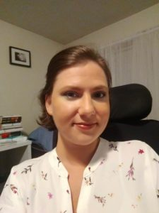 A white woman with short brown hair pinned back and smiling at the camera. She is wearing a white blouse with pink, red, yellow and green flowers. A black wheelchair headrest call be seen behind her head.