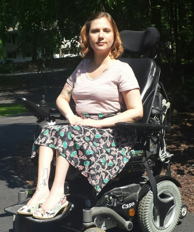 A white woman with short blonde hair is pictured outside. She is wearing a pink tee-shirt, black skirt with pink and green design, and matching heels. She is smiling toward the camera and seated in a black power wheelchair.