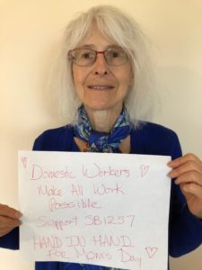 "White woman with grey hair and glasses smiling holding a sign that reads ""Domestic Workers make all work possible. Support SB1257"""