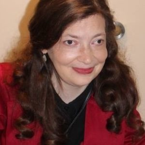Headshot of white woman with long red hair wearing a red jacket and black shirt