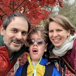 Image of a white mother and father smiling with son with a disability in a wheelchair