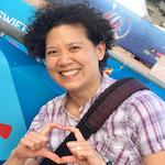 Image of asian women with short curly hair smiling making a heart symbol with her hand