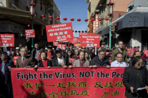 Image of Asian Americans marching with signs that say Reject Fear and Racism, Fight the virus not the people