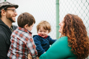 Image of white father and mother with two boys smiling and looking at one another