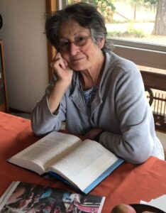Image of white women with short grey hair with oxygen tube in her nose sitting in front of a book looking at the camera and gently smiling.