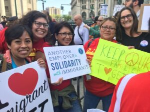 """Group photo of people smiling holding signs at a rally that read """"Another Employer in Solidarity with Immigrants, Keep Our Families Together"""