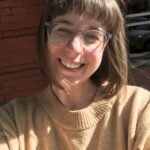 Image of white woman smiling with clear glasses and shoulder length light brown hair wearing a tan sweater. She is outside sunlights is hitting her face.