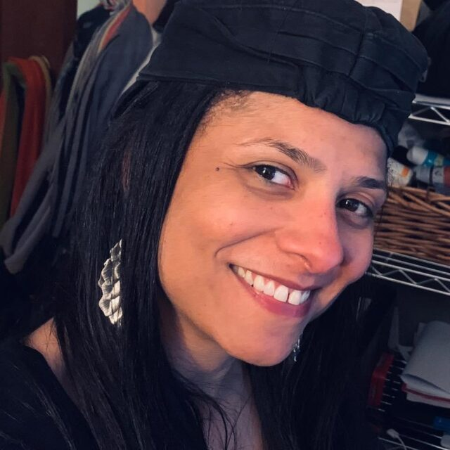 Headshot of black woman smiling looking at the camera with long black hair, dangling silver earrings, and a black hat.