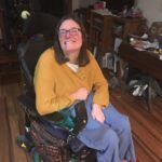 Image of smiling white woman with glasses and long brown hair sitting in a wheelchair with yellow sweater and blue pants