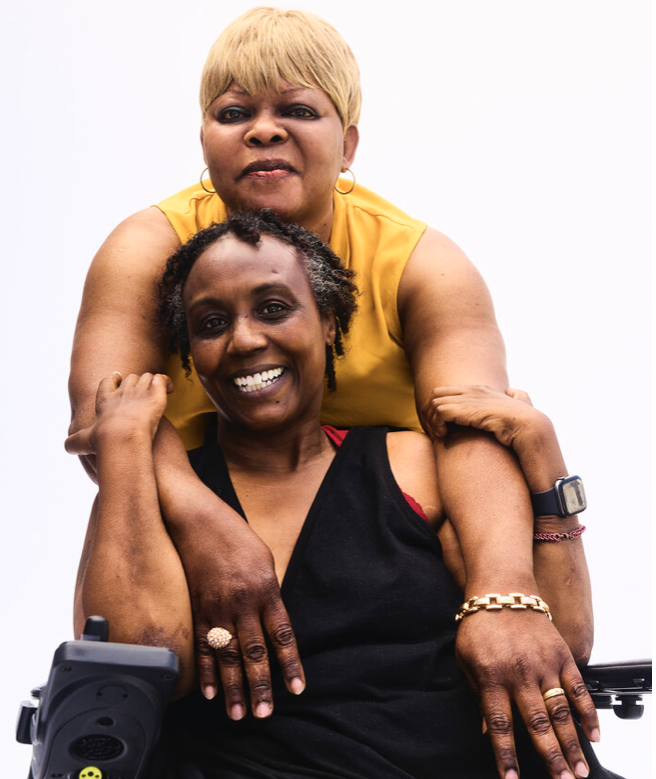 Black women in wheelchair embraces woman standing behind her
