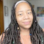 Image of black woman with long dreadlocks smiling and looking directly in the camera. Wearing a peach colored shirt and silver necklace.