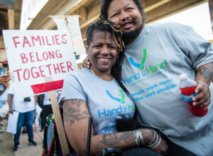 woman in wheelchair with young man hugging her and a sign with text Families Belong Together