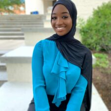 A young black woman who is wearing a black hijab, blue blouse, and black pants is sitting outside.