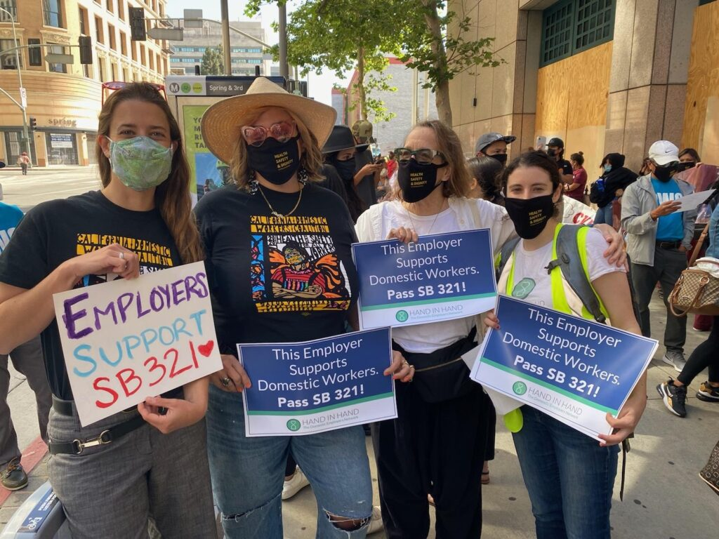 Four white women wearing masks pose for the camera holding signs the say This Employer Supports Domestic Workers. Pass SB321