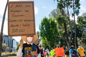 """white women wearing a mask and straw hat and marching and holding a sign that says """"I am an employer who supports domestic worker health and safety"""""""
